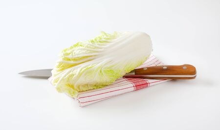 Fresh Chinese cabbage and kitchen knife on dish towel