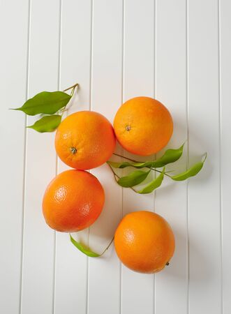 Four whole ripe oranges and leaves Standard-Bild