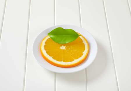 Thin slice of fresh orange on white plate