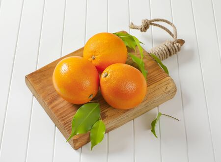 Three whole ripe oranges and leaves on cutting board Standard-Bild