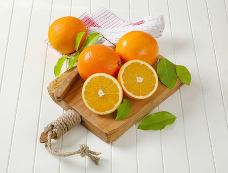 Whole ripe oranges and two halves on cutting board