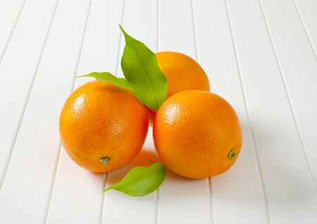 Three whole ripe oranges and leaves Standard-Bild
