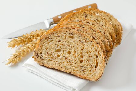 Sliced loaf of whole grain bread on white napkin, wheat ears and kitchen knife next to it Zdjęcie Seryjne