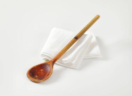 Old wooden cooking (stirring) spoon on white napkin