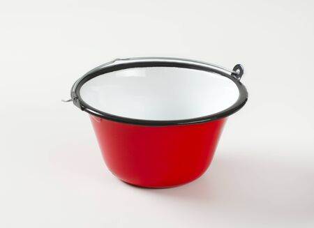 Red enamel cauldron / cooking pot used for outdoor cooking over an open fire and serving goulash, soups, sauces, mulled wine, dips, cheese fondue