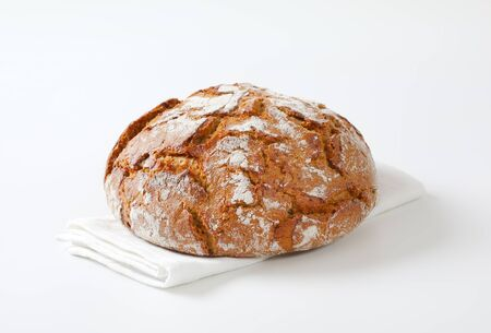 Loaf of rustic sourdough bread on white napkin Standard-Bild