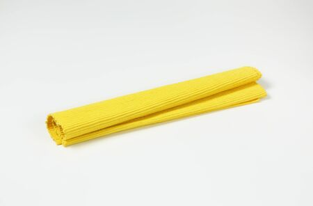 Folded yellow woven cotton place mat
