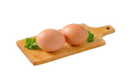 Two brown eggs on wooden cutting board isolated on white