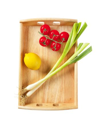 Spring onion, tomatoes and lemon on wooden serving tray isolated on white