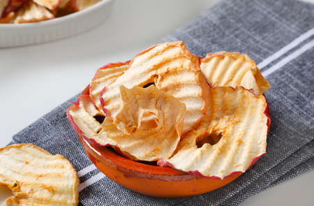 Bowl of dried apple slices - apple chips or rings - on gray napkin