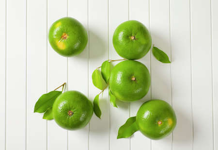 Five whole sweetie fruits (green grapefruits, pomelits) and leaves