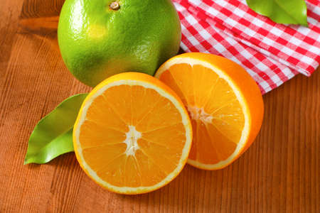 Green grapefruit (sweetie, pomelit, oroblanco), two orange halves and checked red and white tea towel on wooden table