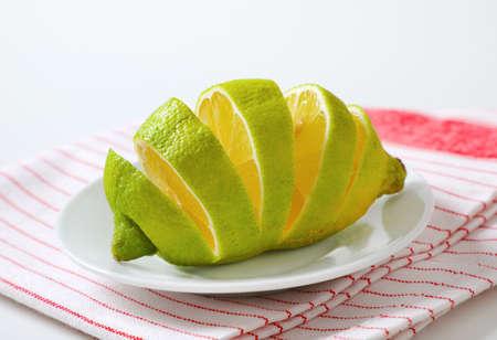 Lemon with green peel and yellow flesh, sliced on white plate Zdjęcie Seryjne