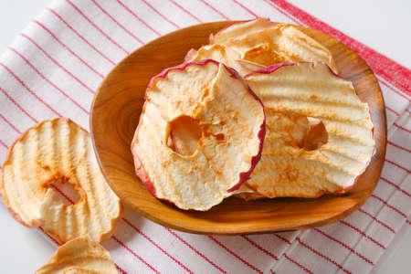 Bowl of dried apple slices - apple chips or rings - on striped tea towel Zdjęcie Seryjne