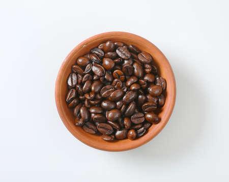 Roasted coffee beans in a terracotta bowl Zdjęcie Seryjne