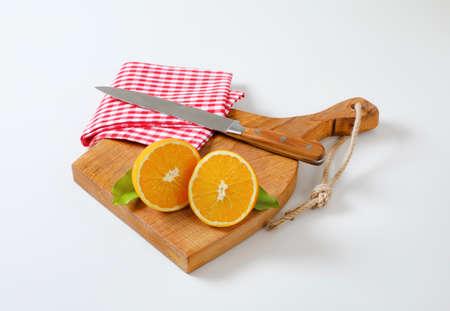 Halved fresh orange, sharp kitchen knife and tea towel on cutting board