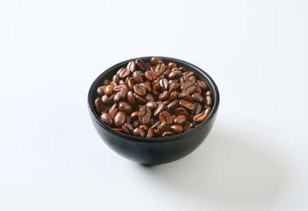 Roasted coffee beans in black bowl