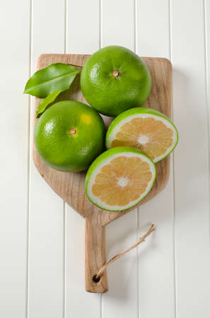 Sweetie fruits (green grapefruits, pomelits) on cutting board
