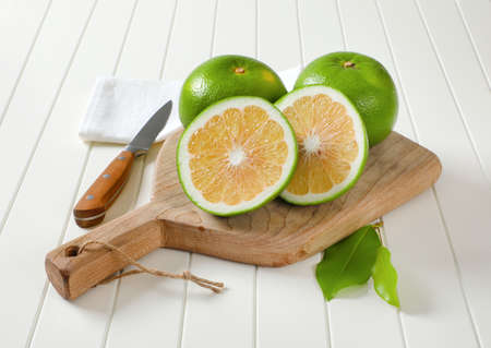 Sweetie fruits (green grapefruits, pomelits) - two whole fruits and slices - on cutting board