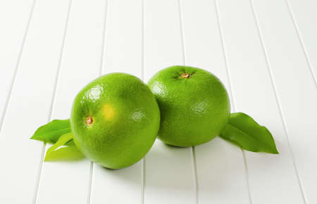Two whole sweetie fruits (green grapefruits, pomelits) and leaves