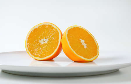 Two fresh orange halves on white plate Zdjęcie Seryjne