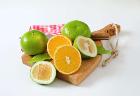 Still life of green grapefruits (sweetie, pomelit, oroblanco grapefruit) and halved orange with knife and tea towel on cutting board