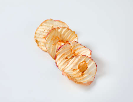 Dried apple slices (apple chips or rings) in a row
