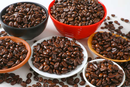 Roasted coffee beans in various bowls and on plate