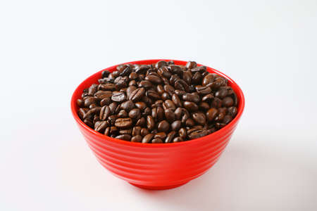 Roasted coffee beans in red bowl
