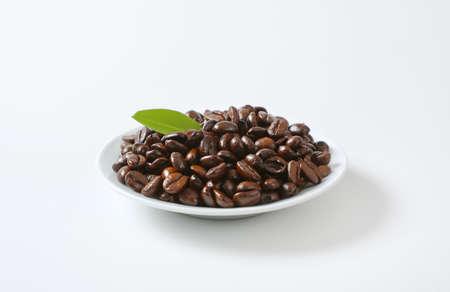 Roasted coffee beans on white plate Zdjęcie Seryjne