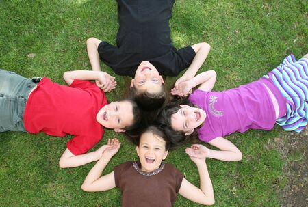 4 Children Lying in the Grass Laughing Out Loud Stock Photo