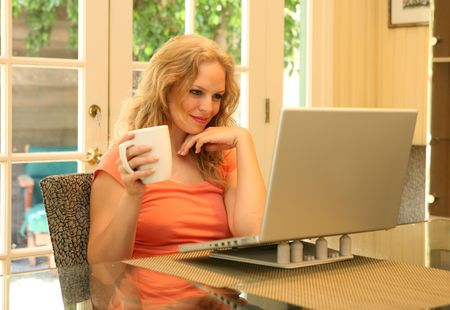 Woman Reading Online While Drinking Coffee