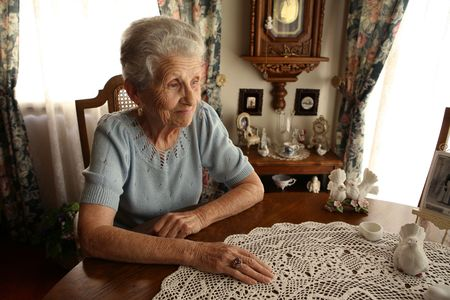 Elderly Senior Citizen Looking Out a Window in Contemplation Stock Photo
