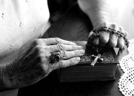 arrepentimiento: Manos de la mujer mayor que sostienen su biblia y rosario