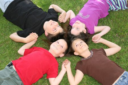 touch down: Four Children Smiling While Lying in the Grass