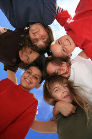 6 Children Hugging Eachother in a Circle and Having Fun Stock Photo
