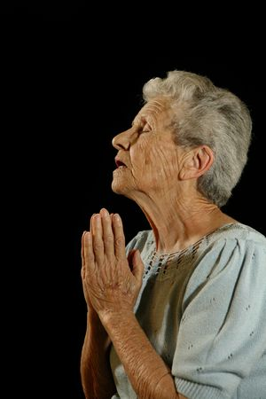 aging face: Old Woman Praying to God on Black