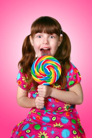 sucker: Bright Pink Image of a Girl Licking a Lollipop on Pink Background
