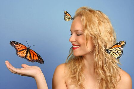 Pretty Woman With Many Butterflies on Blue Background photo