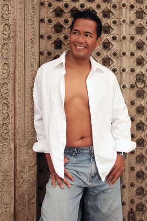 Smiling Happy Asian Male With White Shirt Open and Chest Exposed Wearing Jeans Stock Photo - 3388351