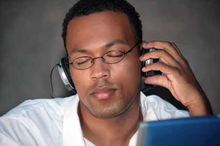 African American Male Listening to Music With Headphones on His Laptop