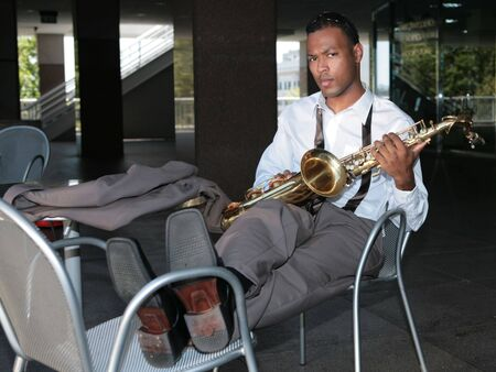 african sax: Serious Saxophone Player Resting Outdoors Stock Photo