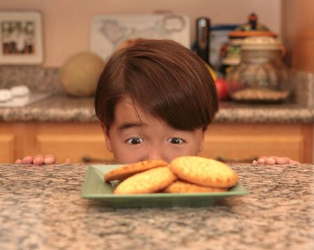 he: Young Asian Boy Looking at Cookies He Wants to Eat