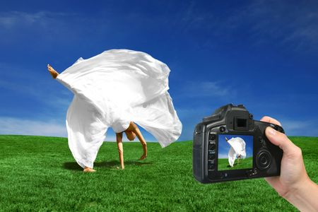 Bride Being Photographed Cartwheeling in the Grass by a Digital Camera photo