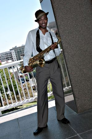Black African Amercian Man Outdoors With a Saxophone In Casual Business Wear photo