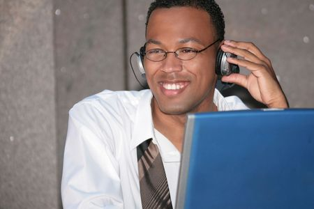 Happy Black Business Man Listening to Music on His Laptop Computer During Lunch Break photo