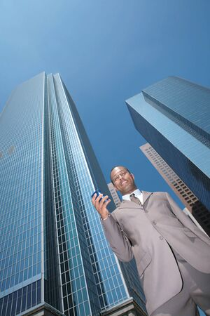 Smiling Black Businessman Checking His Email on a Mobile Device With Offices in the Background photo
