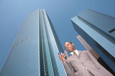 black business man: Voir le r�sum� de la Black Business Man en costume Outdoors regardant Cell Phone