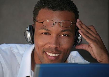 Smiling Black Businessman Listening to Music With Headphones While Working photo