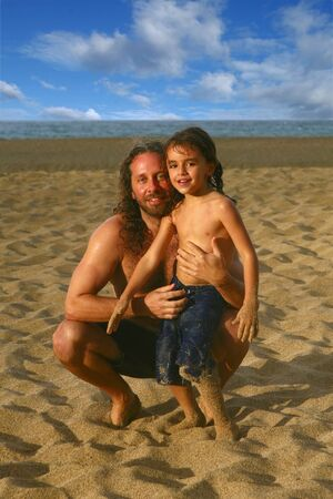 Happy Father and Son on the Beach at Sundown photo
